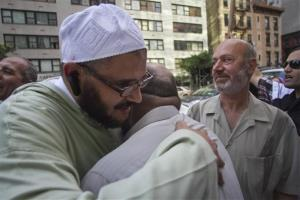 Zein Rimawi, 59, second from right, a leader and founder of the Islamic Society of Bay Ridge mosque, waits to meet with the mosque's former spiritual leader Sheik Reda Shata, left, who is embraced during a protest on Friday, Aug. 16, 2013, in New York, supporting ousted Egyptian president Mohamed...