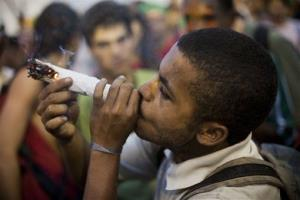 A man smokes a big joint at a demonstration in support of legalizing marijuana during the Rio 20 United Nations Conference on Sustainable Development in Rio de Janeiro, Brazil, Tuesday, June 19, 2012.