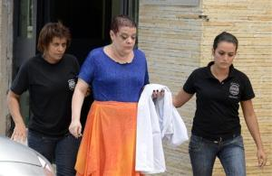 In this Feb. 19, 2013 photo, Virginia Soares de Souza, center, is escorted by police officers to a temporary prison in Curitiba, Parana state, Brazil.
